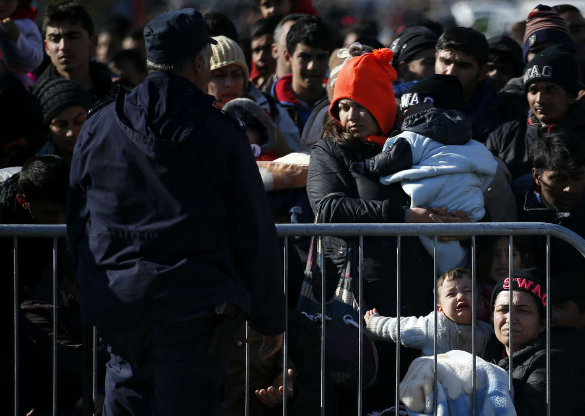 Migrants wait to register with the police at a refugee center in the southern Serbian town of Presevo, Monday, Nov. 16, 2015. Refugees fleeing war by the tens of thousands fear the Paris attacks could prompt Europe to close its doors, especially after police said a Syrian passport found next to one attacker's body suggested its owner passed through Greece into the European Union and on through Macedonia and Serbia last month. (AP Photo/Darko Vojinovic)
