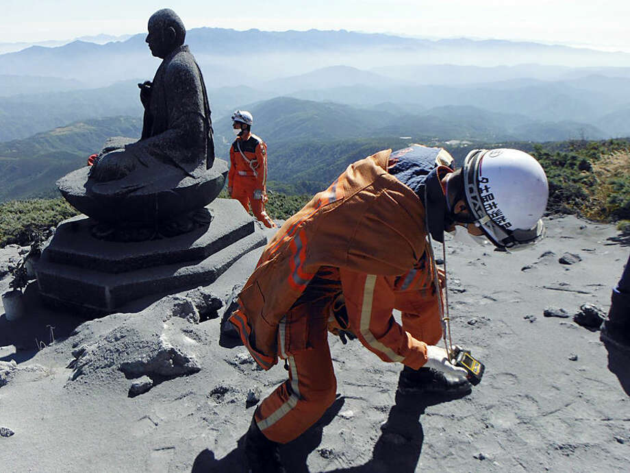 In this Sunday, Sept. 28, 2014 photo released by Nagoya City Fire Dept., a Nagoya City firefighter uses a gas analyzer to check toxic volcanic fumes next to a Buddha statue near the summit of the Mount Ontake in central Japan. Increased seismic activity raised concern Tuesday, Sept. 30, about the possibility of another eruption at the Japanese volcano where dozens of people were killed by Saturday's initial eruption, forcing rescuers to suspend plans to try to recover at least two dozen bodies still near the summit. (AP Photo/Nagoya City Fire Dept.) EDITORIAL USE ONLY