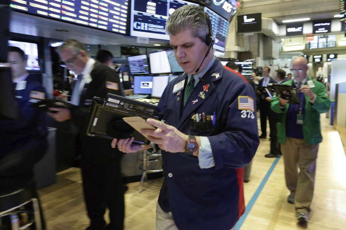 Trader John Panin, center, works on the floor of the New York Stock Exchange, Monday, Nov. 16, 2015. U.S. stocks are opening slightly higher as markets around the world are holding up better than many expected in the wake of the terrorist attacks in Paris. (AP Photo/Richard Drew)