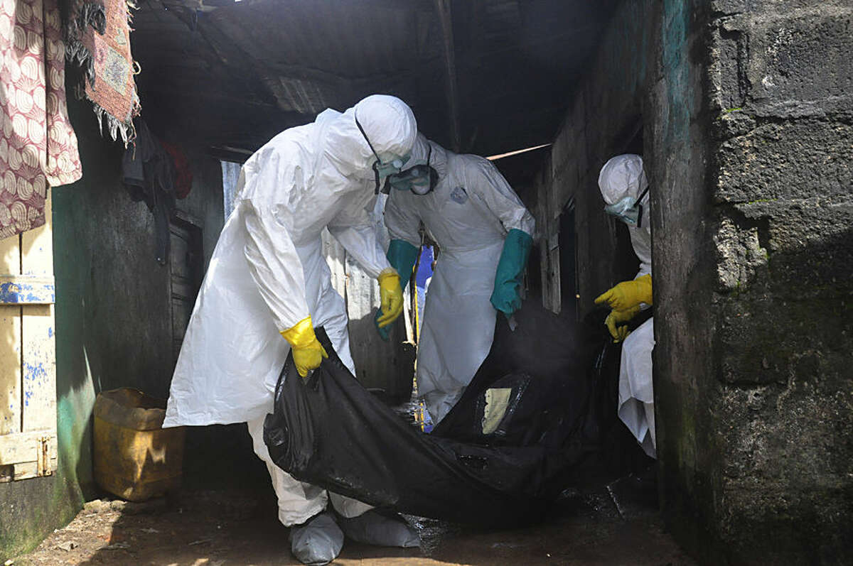 Health workers in protective gear remove the body of a woman suspected to have died from the Ebola virus, near the area of Freeport in Monrovia, Liberia, Wednesday, Oct. 1, 2014. The first case of Ebola diagnosed in the U.S. has been confirmed in a man who recently traveled from Liberia to Dallas, sending chills through the area's West African community whose leaders urged caution to prevent spreading the virus. (AP Photo/Abbas Dulleh)