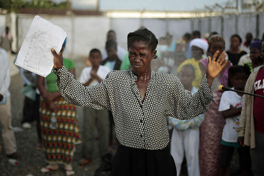 FOR USE AS DESIRED, YEAR END PHOTOS - FILE - A woman being discharged from the Island Clinic Ebola treatment center in Monrovia, Liberia, is sprayed with disinfectant, Tuesday Sept. 30, 2014. (AP Photo/Jerome Delay, File)