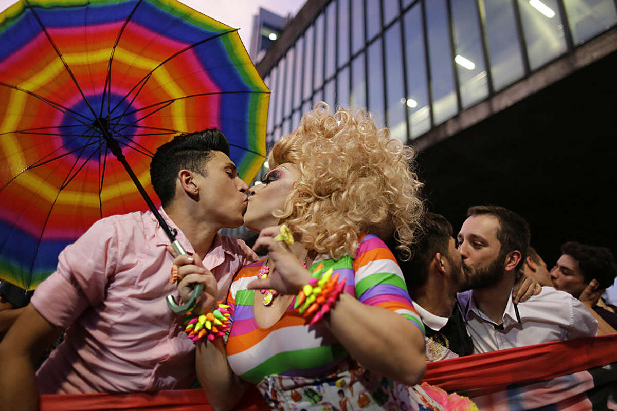 Men kiss during a protest against the homophobic comments of presidential candidate Levy Fidelix, in Sao Paulo, Brazil, Tuesday, Sept. 30, 2014. Fidelix a minor character in Brazil's election race faced a firestorm of criticism on Monday after saying during a presidential debate that the country needs to stand up against gay people who should receive psychological help far away from the general population. The comments drew no reaction from the leading candidates during the nationally televised debate late Sunday. But online and on social media tens of thousands of people denounced Fidelix as homophobic and hateful. (AP Photo/Nelson Antoine)
