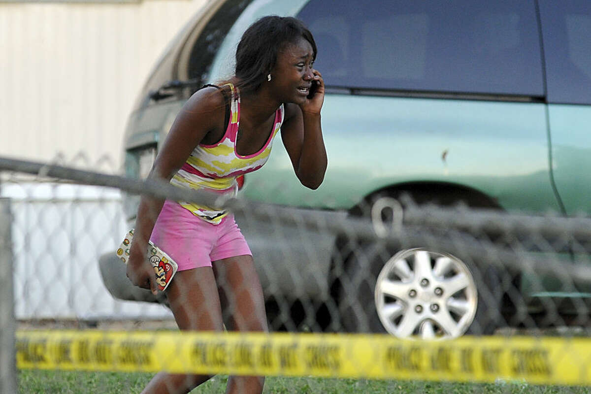A woman reacts after receiving news that a loved one was killed during a shooting near a mobile home community on Athens east side behind the Airport Minit Market on Tuesday, Sept. 30, 2014, in Athens, Ga. Athens-Clarke County police Maj. Clarence Holeman tells the Athens Banner-Herald details on the circumstances that led to the shooting are unclear and authorities are working to determine what led up to the gunfire. (AP Photo/The Banner-Herald, AJ Reynolds)