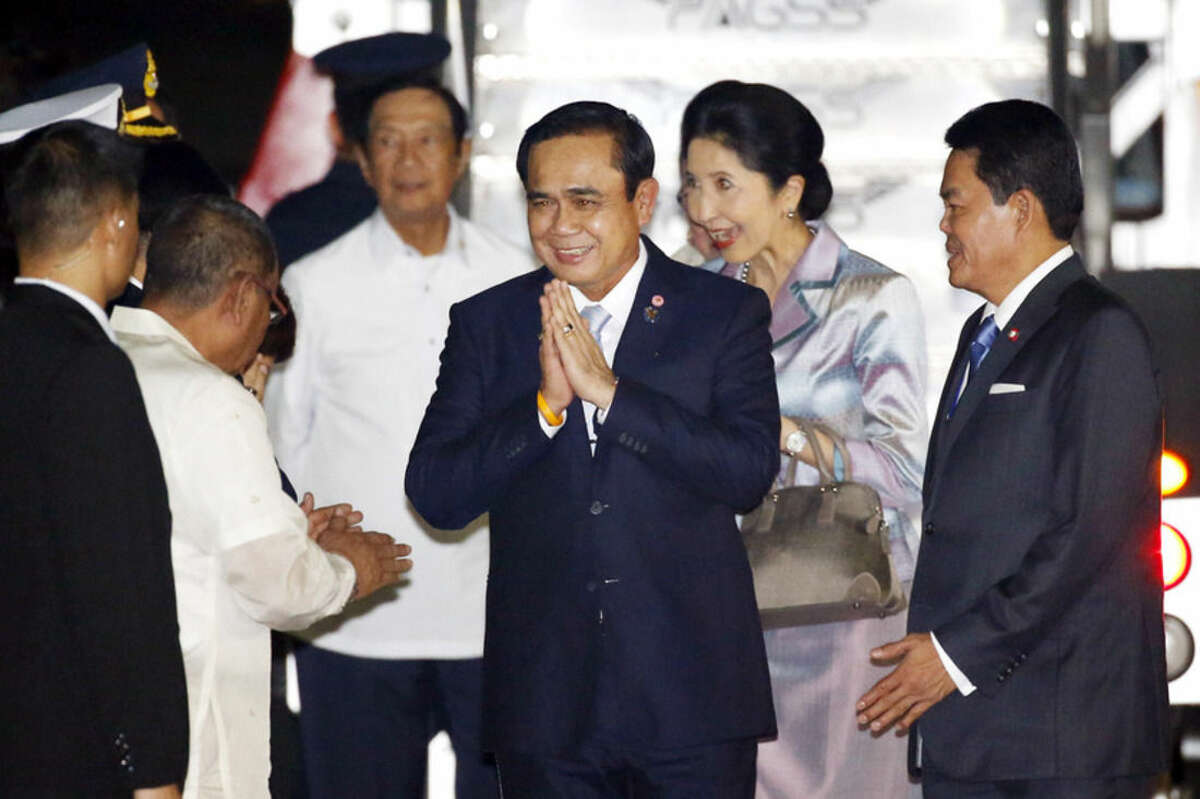 Thailand's Prime Minister General Prayut Chan-o-Cha, center, offers a traditional Thai greeting or