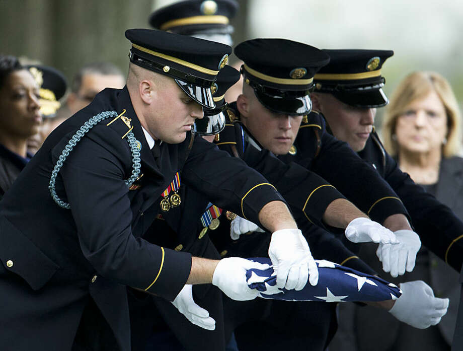 Army honor guards pass the folded flag that draped the coffin containing the remains of U.S. Army Maj. Michael J. Donahue during a burial services at Arlington National Cemetery in Arlington, Va., Tuesday, Sept. 30, 2014. According to the Department of Defense, Maj. Donahue of Columbus, Ohio, died Sept. 16, in Kabul, Afghanistan, of wounds suffered from an enemy attack. He is assigned to the Headquarters and Headquarters Battalion, XVIII Airborne Corps, Fort Bragg, N.C. (AP Photo/Manuel Balce Ceneta)
