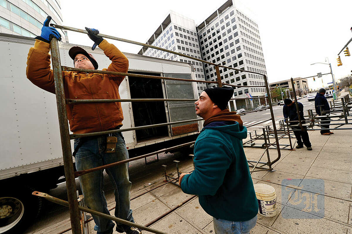 Workers with Lighting and Decorating Inc., including Ernesto and Arturo Fontana, set up bleachers along Atlantic Street in Stamford Wednesday in preparation for this weekend's UBS Parade Spectacular.