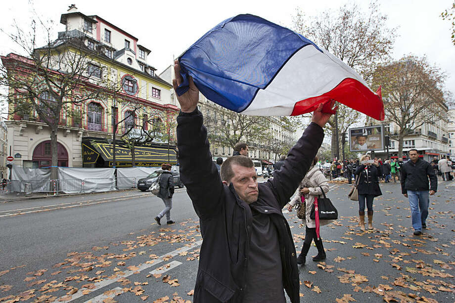 A man displays the French flag in front of the Bataclan concert hall, which was a site of last Friday's attacks, in Paris, Tuesday, Nov. 17, 2015. France is demanding security aid and assistance from the European Union in the wake of the Paris attacks and has triggered a never-before-used article in the EU's treaties to secure it. (AP Photo/Peter Dejong)