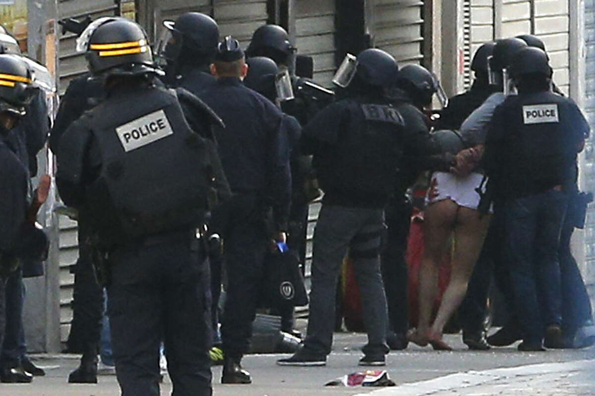 Police forces arrest a man in Saint-Denis, a northern suburb of Paris, Wednesday, Nov. 18, 2015. Police say two suspects in last week's Paris attacks, a man and a woman, have been killed in a police operation north of the capital. Two police officers have been injured in the standoff. Police have said the operation is targeting the suspected mastermind of last week's attacks, believed to be holed up in an apartment in Saint-Denis with several other heavily armed suspects. (AP Photo/Christophe Ena)