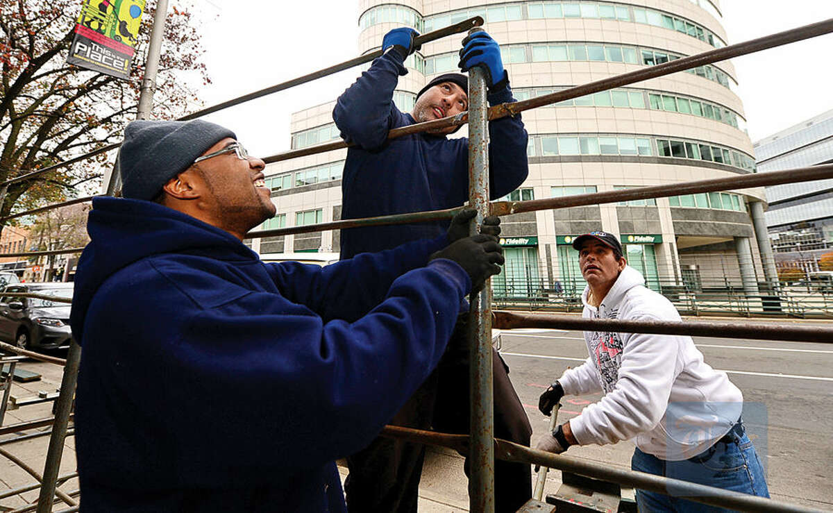 Workers with Lighting and Decorating Inc., including Dwight Smith, Nick Carabello and Gilbert Luna, set up bleachers along Atlantic Street in Stamford Wednesday in preparation for this weekend's UBS Parade Spectacular.