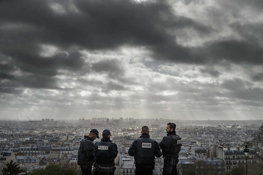 French Police officers stand on guard near the church of Sacre Coeur, on top of the Montmartre hill with Paris, Wednesday, Nov. 18, 2015. A woman wearing an explosive suicide vest blew herself up Wednesday as heavily armed police tried to storm a suburban Paris apartment where the suspected mastermind of last week's attacks was believed to be holed up, police said. (AP Photo/Daniel Ochoa de Olza)