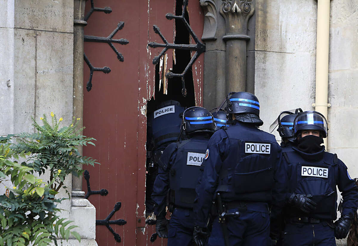 French police officers storm a church after a raid in Paris suburb Saint-Denis, Wednesday, Nov.18, 2015. A woman wearing an explosive suicide vest blew herself up Wednesday as heavily armed police tried to storm a suburban Paris apartment where the suspected mastermind of last week's attacks was believed to be holed up, police said. (AP Photo/Thibault Camus)