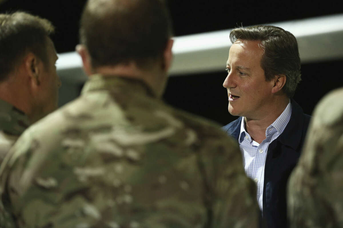 British Prime Minister David Cameron meets pilots, engineers and logistic support staff in front of a Tornado GR4 at RAF Akrotiri base, Cyprus, Thursday, Oct. 2, 2014. The prime minister flew to the RAF base in Akrotiri on Thursday and will meet British pilots taking part in air strikes against Islamic State group targets in Iraq. (AP Photo/Dan Kitwood, Pool)