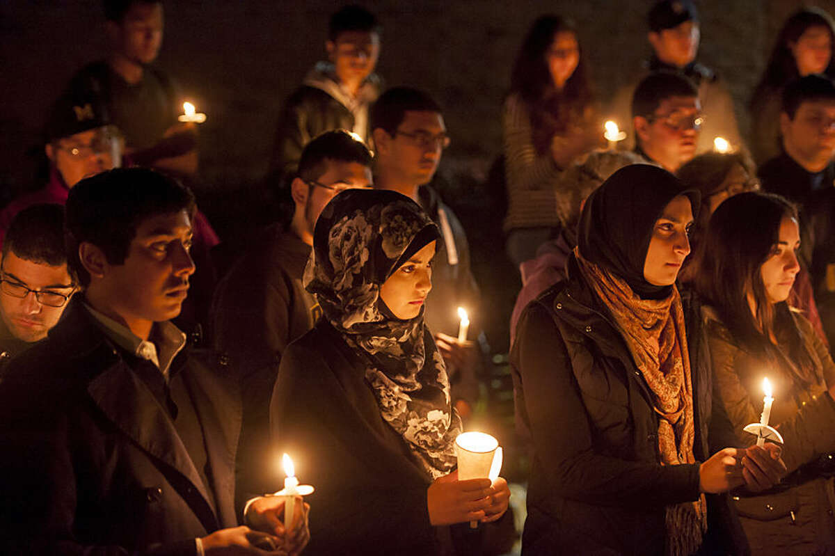 People gather outside the University Center on the campus of the University of Michigan-Dearborn on Monday, Nov. 16, 2015 in Dearborn, Mich. University campuses in Michigan are among places in the state where vigils have taken place for victims of violence including the deadly attacks in Paris. (David Guralnick/Detroit News via AP) DETROIT FREE PRESS OUT; HUFFINGTON POST OUT; MANDATORY CREDIT