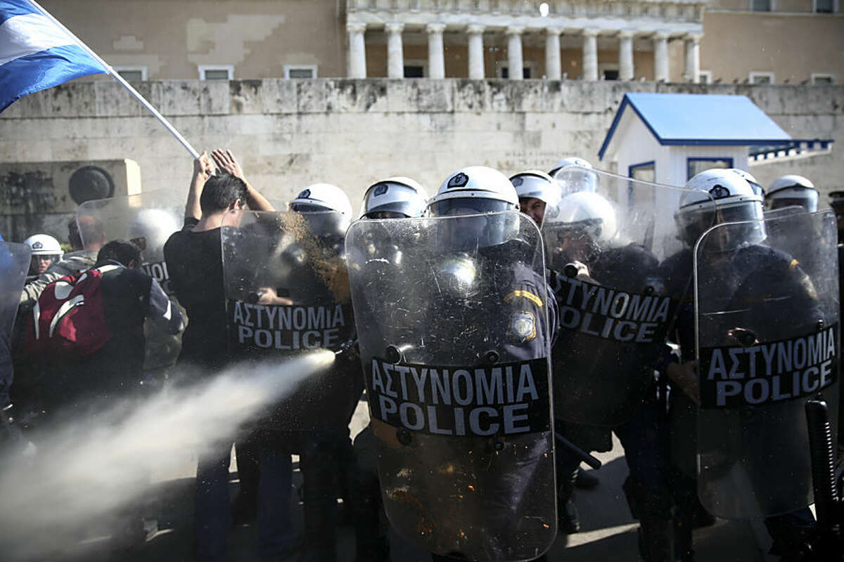 Policemen spray tear gas against farmers during an anti-government protest in front of the parliament at central Syntagma square in Athens, Wednesday, Nov. 18, 2015. Greek farmers protesting over planned tax and pension reforms demanded by the country's bailout creditors have clashed outside parliament with police, who used tear gas to disperse them. (AP Photo/Yorgos Karahalis)