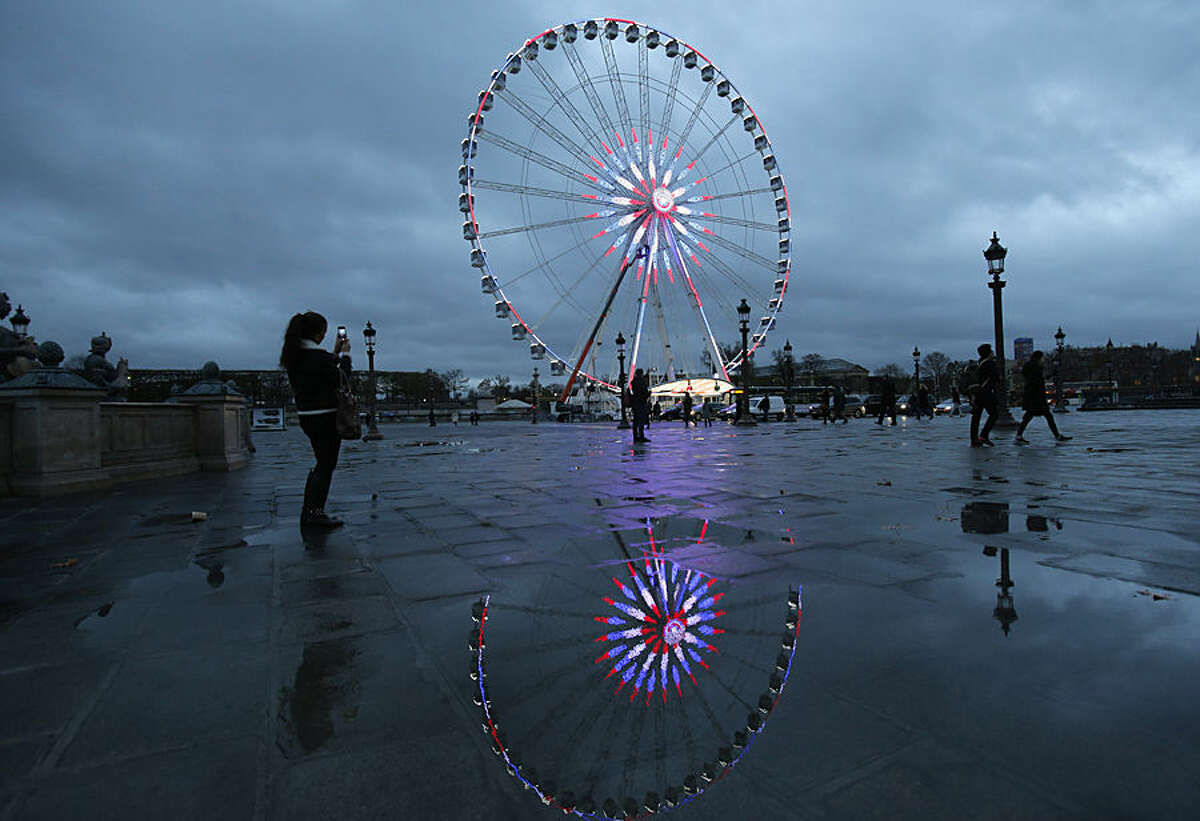 A woman pictures the ferris wheel illuminated with the French colors on the Concorde square in Paris, Tuesday, Nov.17, 2015. France invoked a never-before-used European Union
