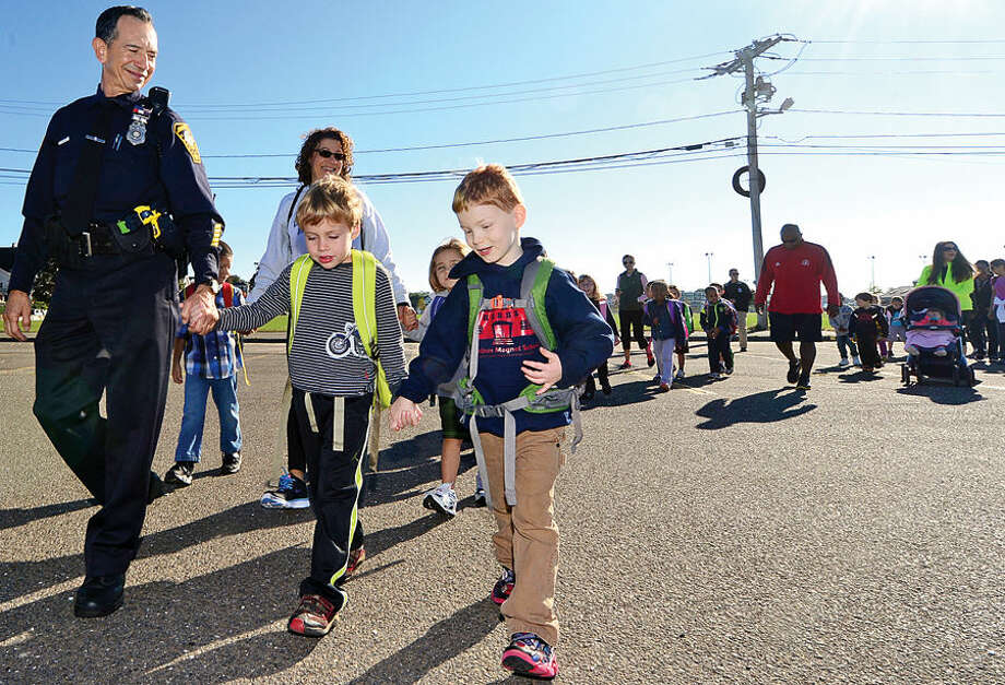 Hour photo / Erik Trautmann Norwalk police officer Cesar Ramirez helps Columbus Magnet School kindergartners Ben Marshall and Charlie Crossland start off on the school's first Walk to School Day with students, staff, parents, Norwalk Health Department staff and the Greater Norwalk Healthy Living Workgroup who walked from Veteran's Memorial Park the the school Friday morning.