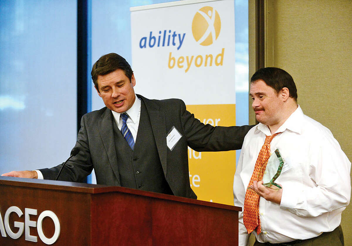 Hour photo / Erik Trautmann Ability Beyond Manager of Corporate Relations Kevin Bielmeier congratulates Longevity Award winner, Chad Tihor of Stop & Shop, as Ability Beyond honors businesses and individuals at the 3rd Annual Corporate Recognition Breakfast at Diageo headquarters on Main Ave in Norwalk Friday.