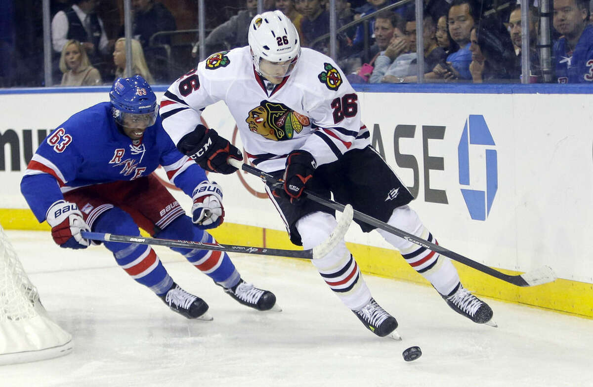 New York Rangers' Anthony Duclair (63) chases Chicago Blackhawks' Michal Handzus (26) during the second period of an NHL preseason hockey game Friday, Oct. 3, 2014, in New York. (AP Photo/Frank Franklin II)