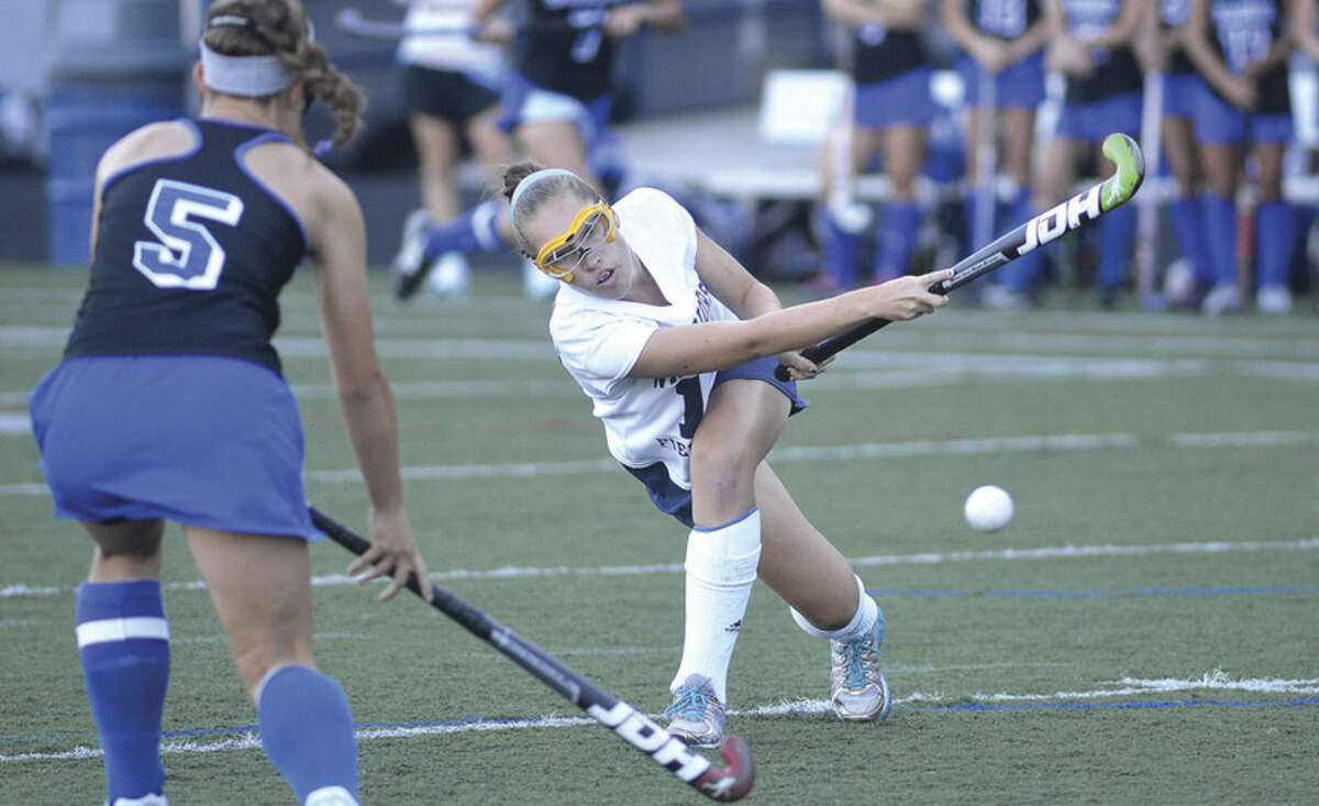 Hour photo/Alex von Kleydorff Wilton's Jillian Mahon takes a shot while Darien's Julia Russo watches on during Friday afternoon's game.