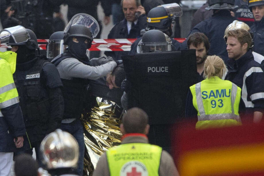Hooded police officers detain a man in Saint-Denis, near Paris, Wednesday, Nov. 18, 2015. A woman wearing an explosive suicide vest blew herself up Wednesday as heavily armed police tried to storm a suburban Paris apartment where the suspected mastermind of last week's attacks was believed to be holed up, police said. (AP Photo/Peter Dejong)