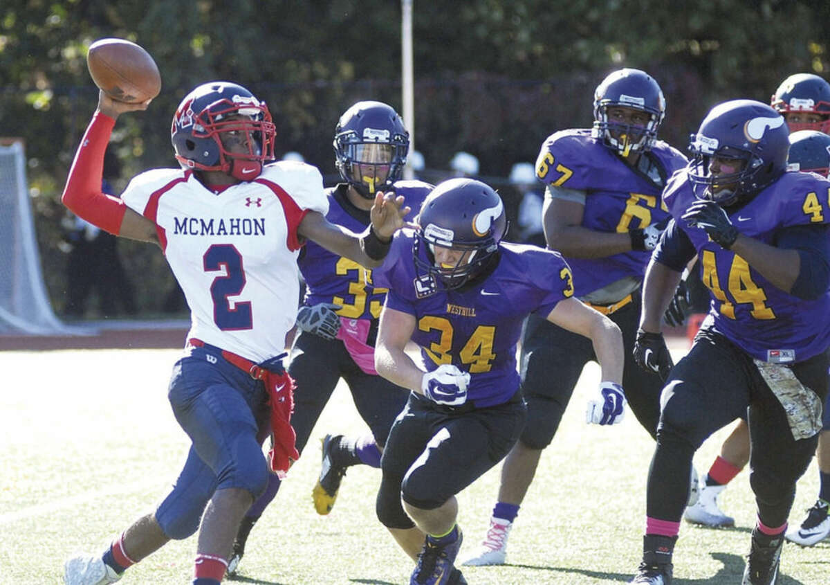 Hour photo/John Nash Brien McMahon quarterback Jason Hall (2) gets off a pass under a heavy Westhill rush that includes, from left, Jacob Scarvey, Joe Schlessinger, Maliek Dawkins and Isiah Ramon. McMahon won the game, 19-14.