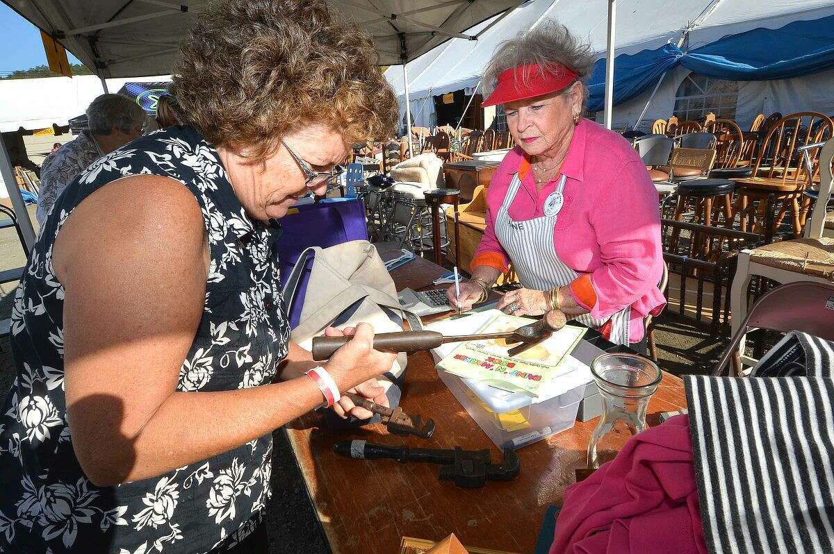Hour Photo/Alex von Kleydorff At Minks to Sinks in Wilton Bobbi Eddinger takes advantage of Friends and Family day to purchase a variety of items, such as tools, frames, clothing and a bicycle from volunteer Anne Atkins