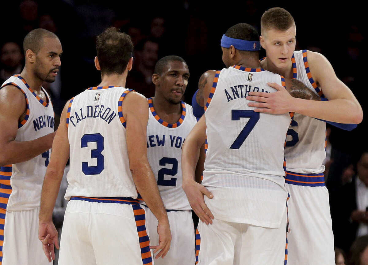 New York Knicks forward Carmelo Anthony (7) hugs New York Knicks forward Kristaps Porzingis (6) as they huddle with guard Arron Afflalo (4), guard Jose Calderon (3) and guard Langston Galloway (2) during the fourth quarter of an NBA basketball game against the Charlotte Hornets, Tuesday, Nov. 17, 2015, in New York. (AP Photo/Julie Jacobson)
