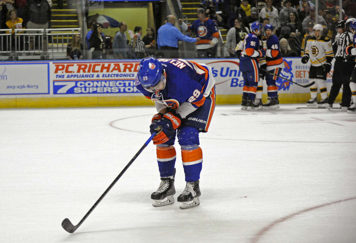 New York Islanders center Brock Nelson (29) leaves the ice after being hit by Boston Bruins defenseman Kevan Miller during the second period of a preseason NHL hockey game in Bridgeport, Conn., on Friday, Oct. 3, 2014. Miller received a five-minute major penalty and a game misconduct for the hit. (AP Photo/Fred Beckham)