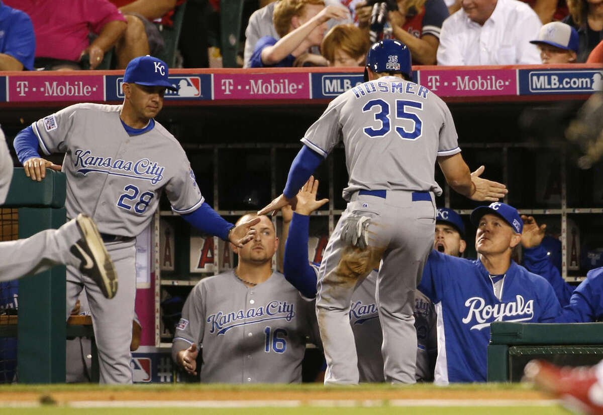 Kansas City Royals Eric Hosmer (35) is greeted in the dugout after he scored on a single by Alex Gordon against the Los Angeles Angels in the second inning of Game 2 of baseball's AL Division Series, in Anaheim, Calif., Friday, Oct. 3, 2014. (AP Photo/Lenny Ignelzi)