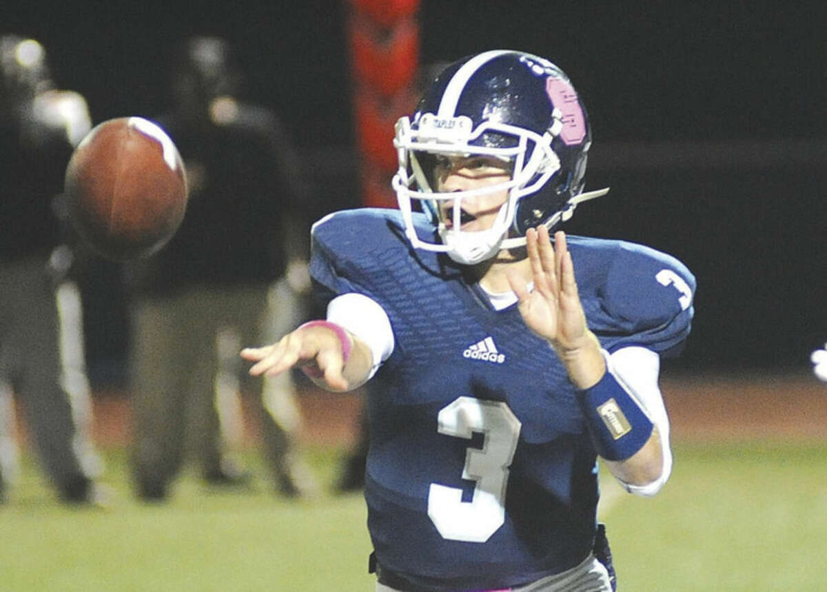Hour photo/John Nash -Staples High School quarterback Teddy Coogan options the ball to one of his running backs during the first quarter of play against Stamford at Staples Field on Thursday night.