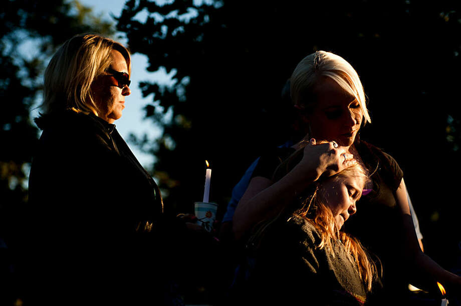 In this photo taken on Thursday, Oct. 2, 2014, Shantay Healey, right, consoles her daughter Annika, 10, during a vigil for the Strack family at Pioneer Park in Provo, Utah. More than 100 family members and friends gathered to remember five members of the Strack family mysteriously found dead at home last weekend. (AP Photo/The Daily Herald, Grant Hindsley) MANDATORY CREDIT