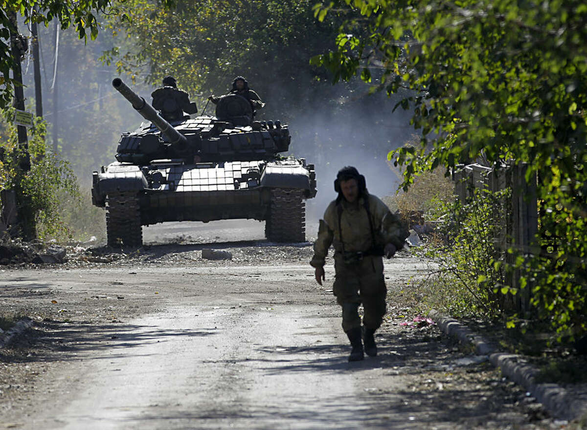 A pro-Russian rebel tank rolls to take position near to the airport in the town of Donetsk, eastern Ukraine, Friday, Oct. 3, 2014. Artillery fire hit Donetsk airport Friday as Pro-Russian rebels are pressing to seize the key airport in eastern Ukraine despite fierce resistance from government forces.(AP Photo/Darko Vojinovic)