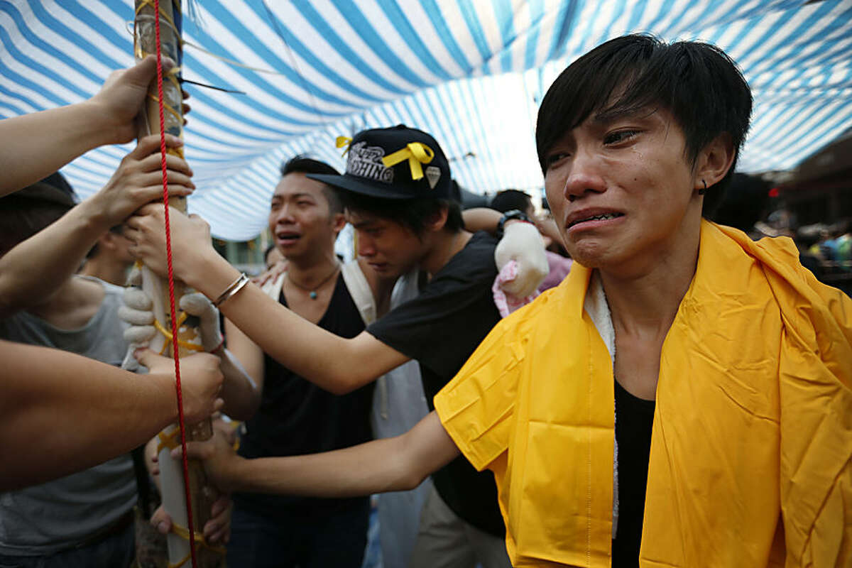 Student protesters are overwhelmed with emotions as they hold onto their tent while being threatened by residents and pro-Beijing supporters in Kowloon's crowded Mong Kok district, Friday, Oct. 3, 2014 in Hong Kong. Clashes broke out Friday as Hong Kong residents and pro-Beijing supporters tried to force pro-democracy activists from the streets they were occupying, reviving the possibility that the weeklong standoff could turn violent despite and attempt by the city's leader to defuse the situation. (AP Photo/Wong Maye-E)