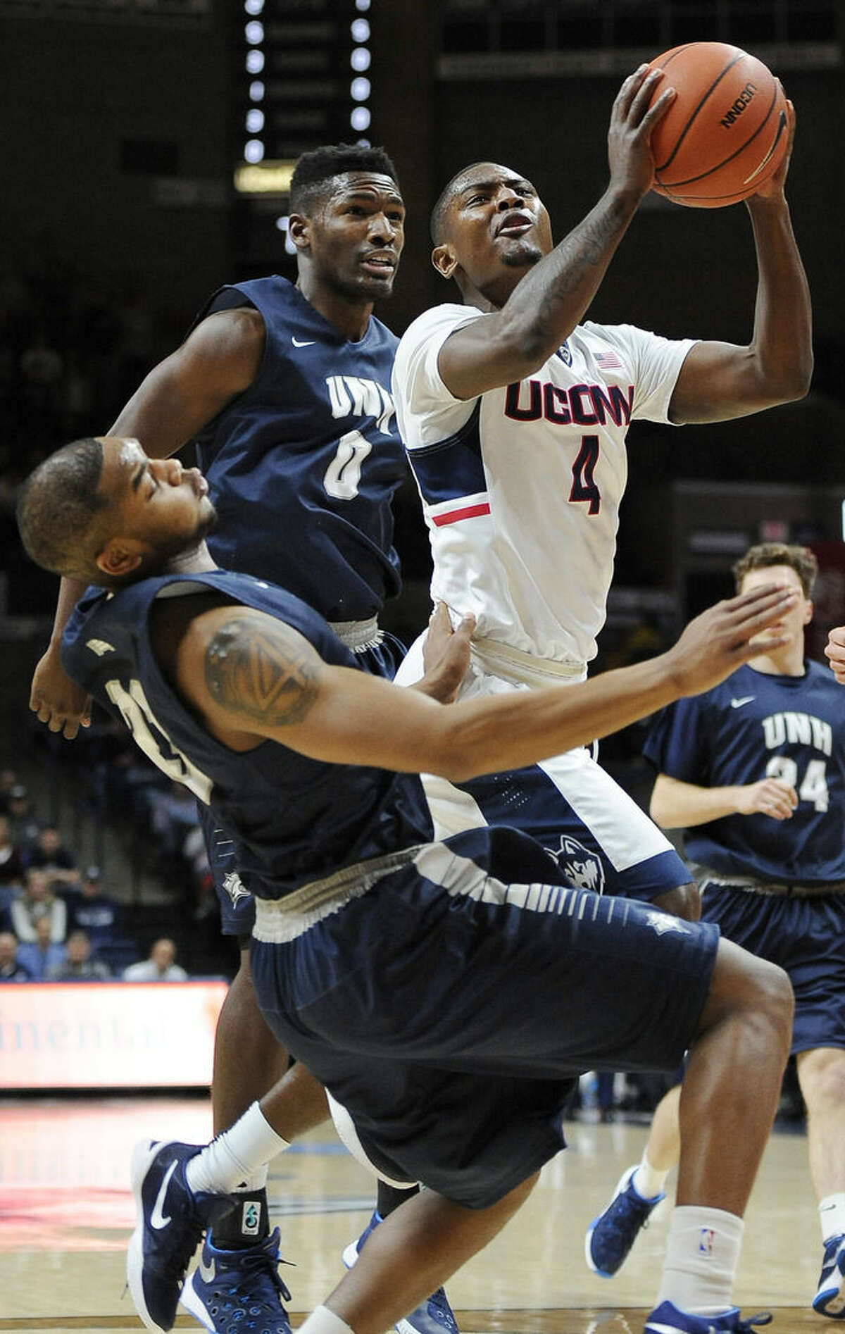 Connecticut's Sterling Gibbs, right, goes up for a basket as he is fouled by New Hampshire's Ronnel Jordan, foreground, as New Hampshire's Jaleen Smith, back defends, in the first half of an NCAA college basketball game, Tuesday, Nov. 17, 2015, in Storrs, Conn. (AP Photo/Jessica Hill)