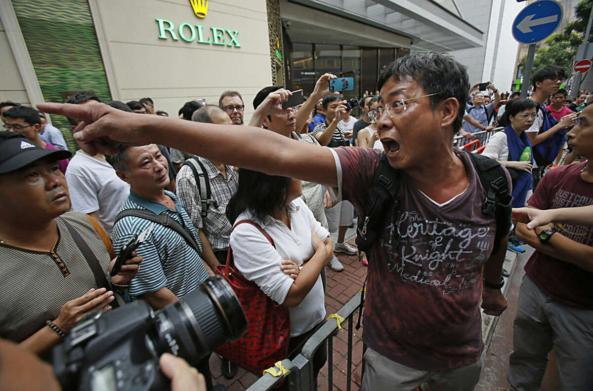 An angry local demands that the pro-democracy student protesters remove the barricades blocking streets in Causeway Bay, Hong Kong, Friday, Oct. 3, 2014. Crowds of pro-democracy protesters on the streets of Hong Kong dwindled sharply Friday after the territory's leader agreed to meet with their leaders over demands for electoral reforms. An afternoon thunderstorm - and sheer exhaustion after the weeklong protests - also appeared to keep people off the streets. (AP Photo/Wally Santana)