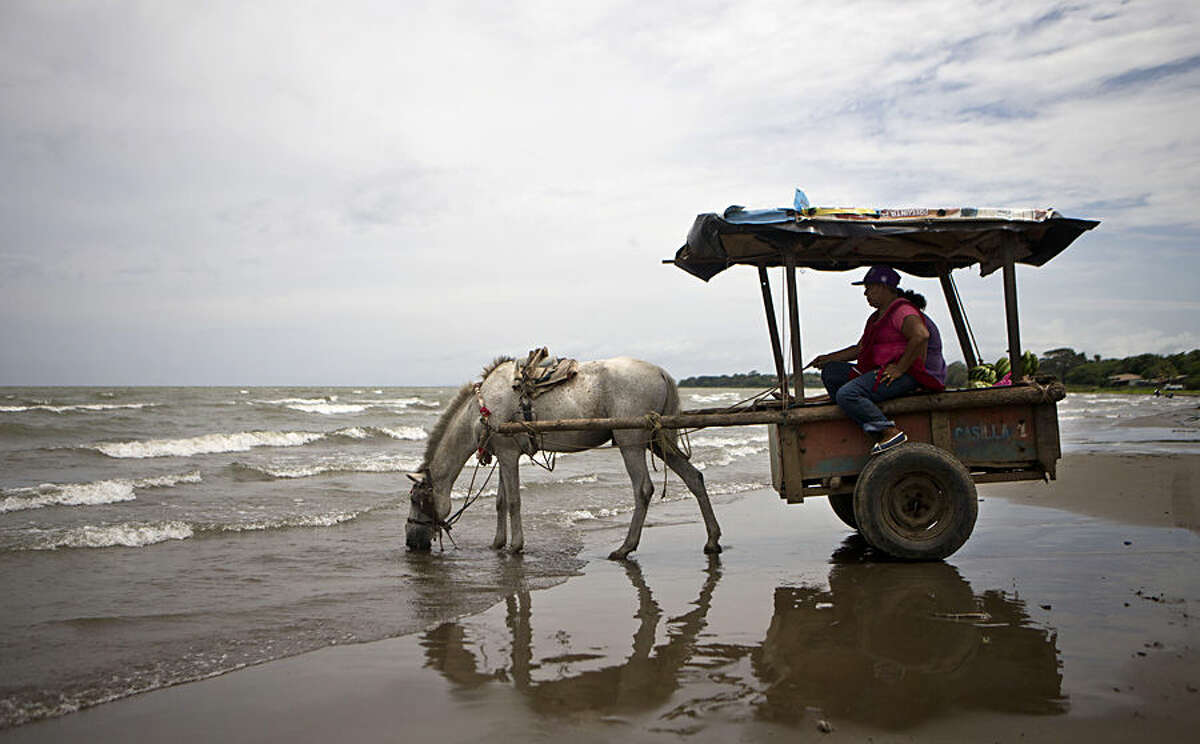 A woman in a handmade wood cart waits while her horse drinks water from the Cocibolca Lake in San Jorge, Nicaragua, Friday, Oct 3, 2014. (AP Photo/Esteban Felix)