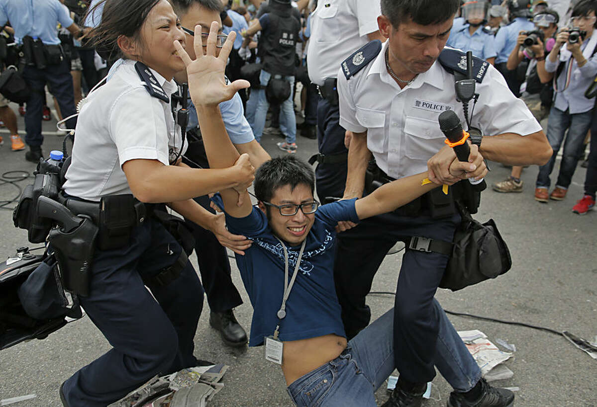 A pro-democracy protester is taken away by police officers as an ambulance tries to leave the compound of the chief executive office in Hong Kong, Friday, Oct. 3, 2014. Hong Kong protesters on Friday welcomed an overnight offer by the territory's leader of talks to defuse the crisis over demonstrations seeking democratic reforms, though they continued to demand he resign and maintained barricades around government headquarters, frustrating staff going to work. (AP Photo/Vincent Yu)