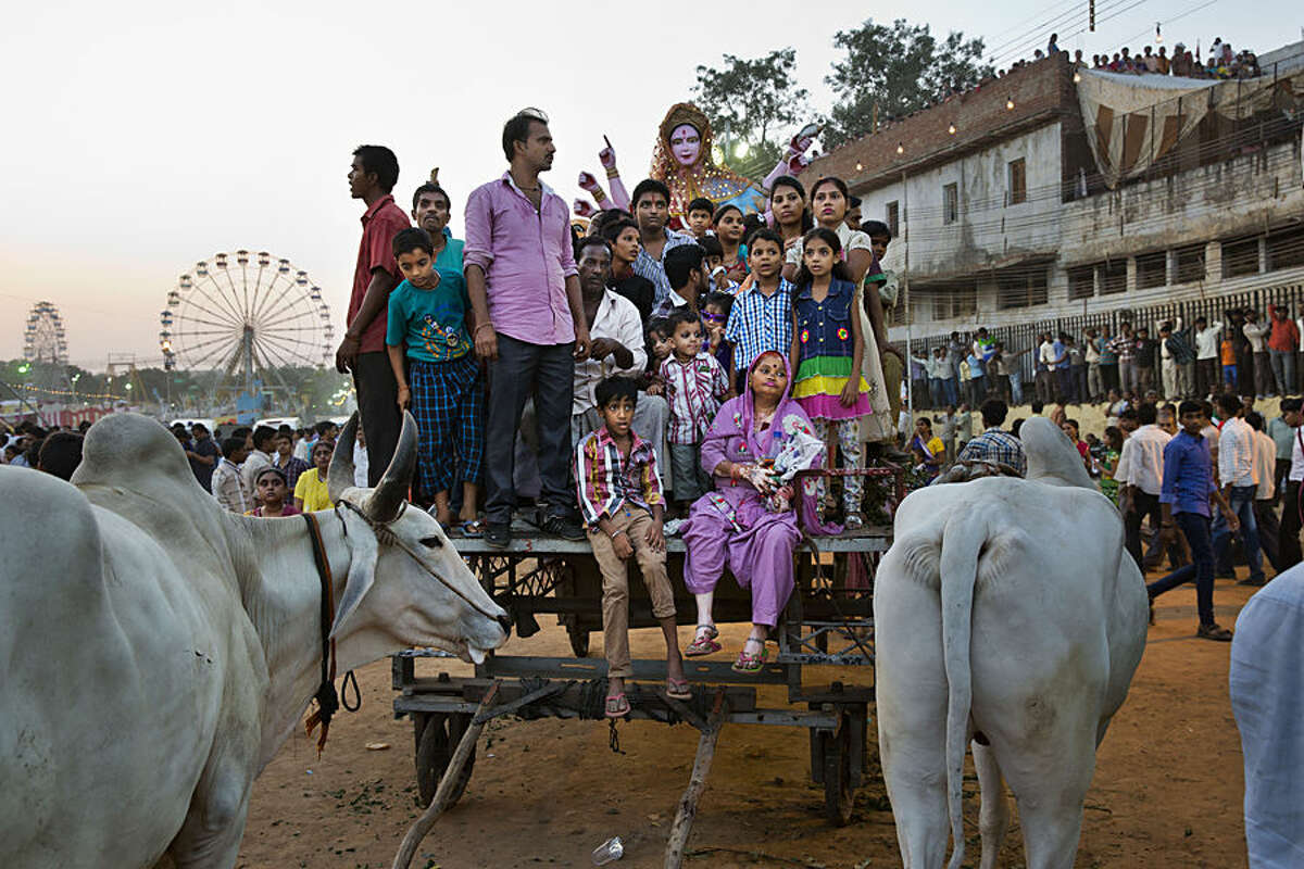 Indians sit on a cart as they gather to watch the burning of effigies of demon king Ravana during Dussehra celebrations at Ramlila ground in New Delhi, India, Friday, Oct. 3, 2014. Dussehra commemorates the triumph of Lord Rama over the demon king Ravana, marking the victory of good over evil. (AP Photo/Bernat Armangue)