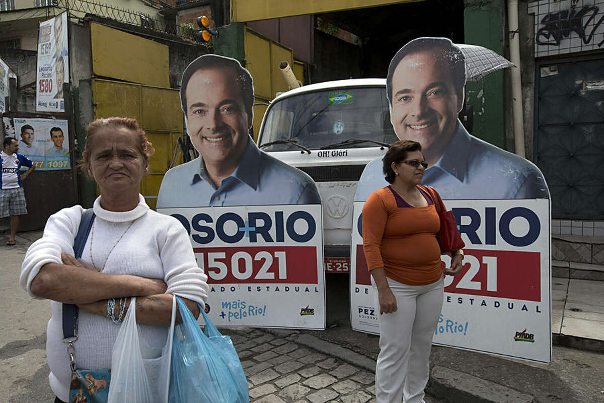 Women wait for transportation at a bus station where campaign signs stand of Carlos Osorio, who is running for Rio de Janeiro state representative in Brazil's National Congress, in the Complexo de Alemao favela of Rio de Janeiro, Brazil, Friday, Oct. 3, 2014. Brazil will hold general elections on Sunday, Oct. 5, 2014. (AP Photo/Silvia Izquierdo)
