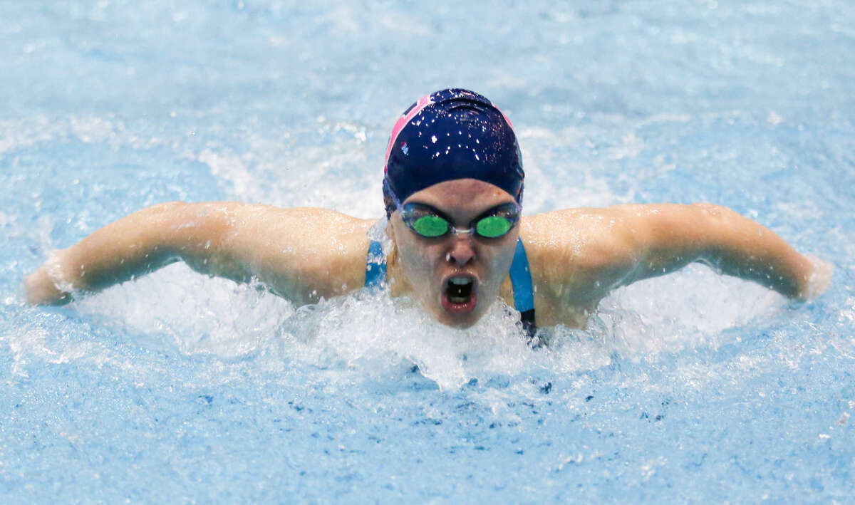Hour photo/Chris Palermo. Staples' Mia Bullock competes in the butterfly race at the CIAC swim championships at Southern Connecticut State University Tuesday night.