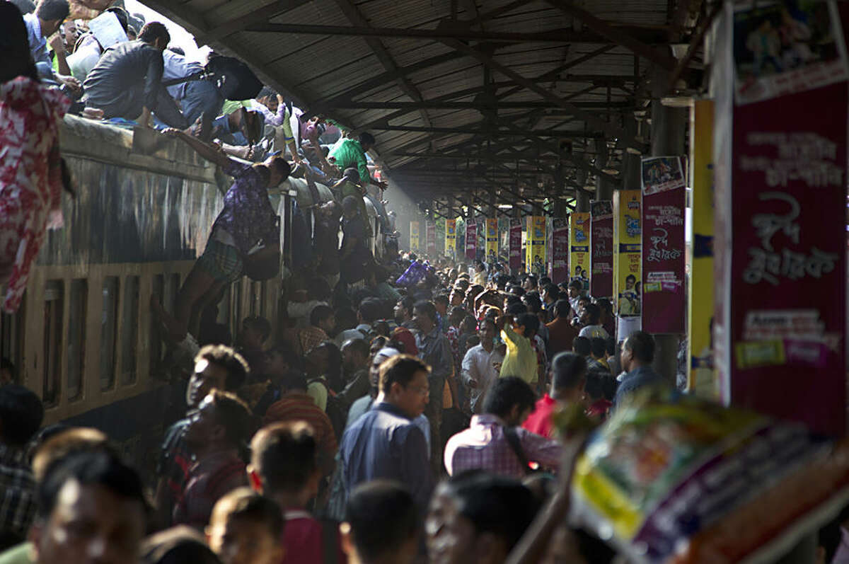 Bangladeshi Muslims try to climb on to the roof of an overcrowded train as they head to their homes ahead of Eid al-Adha in Dhaka, Bangladesh, Friday, Oct. 3, 2014. Muslims around the world are preparing to celebrate Eid al-Adha, a three-day holiday that starts Saturday, commemorating the willingness of the prophet Ibrahim - or Abraham as he is known in the Bible - to sacrifice his son in accordance with God's will, though in the end God provides him a sheep to sacrifice instead. (AP Photo/A.M. Ahad)