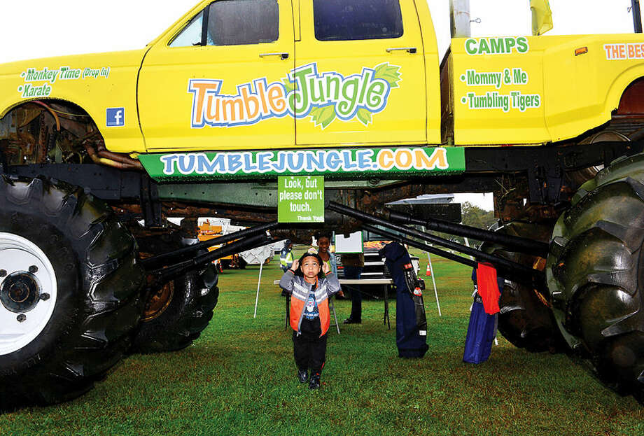 Hour photo / Erik Trautmann 4 year old Julez Vlicky goes under the Tumble Jungle monster truck during the Human Services Council's third annual KIDZFEST Touch-A-Truck Fundraiser to benefit Children's Connection Saturday at Taylor Farm Park. KIDZFEST raises funds to support Children's Connection, a nationally accredited Children's Advocacy Center that works to identify, substantiate, and treat cases of sexual and severe physical abuse while working toward its mission of creating a world where no child is harmed and no family is left without guidance.