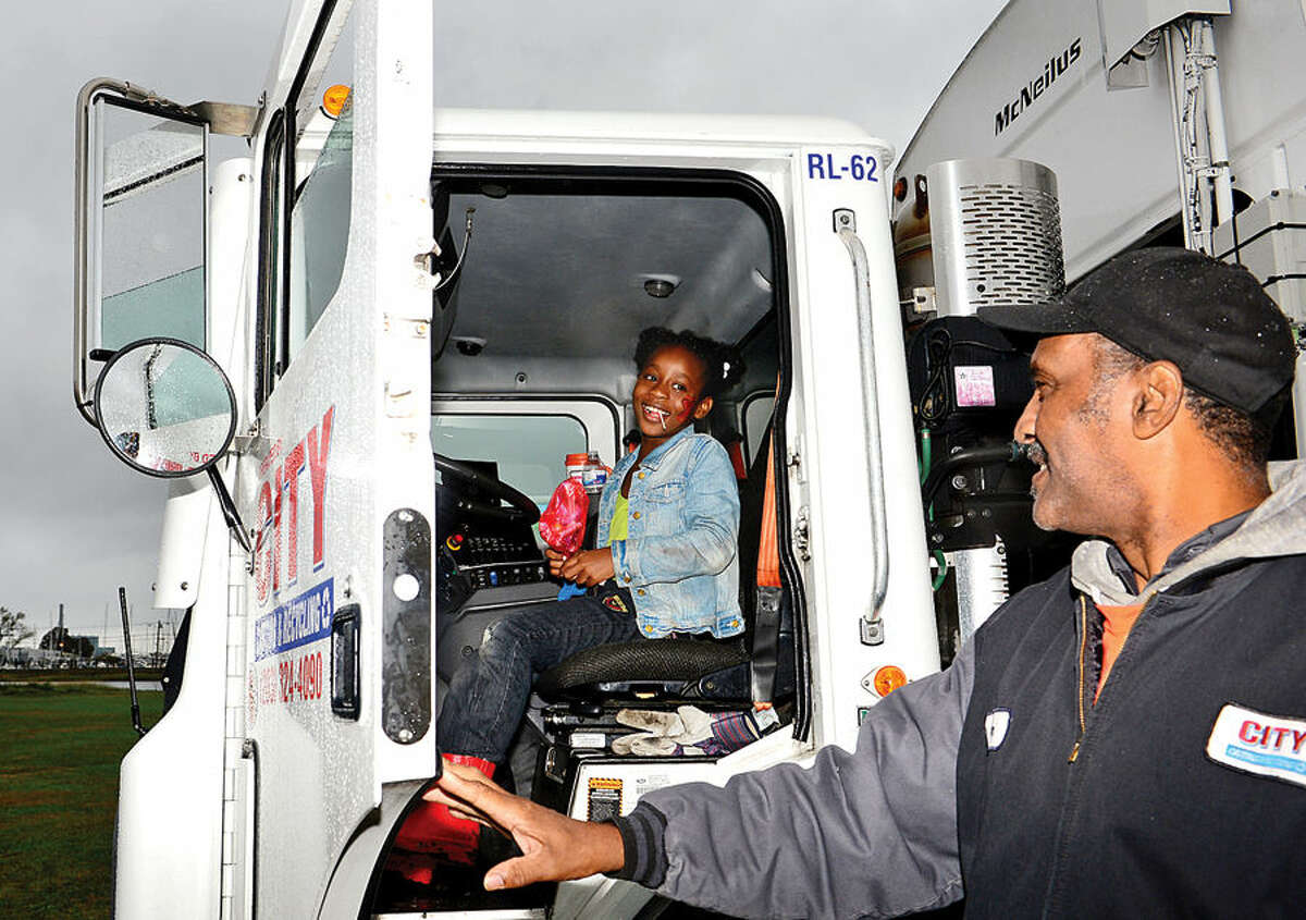 Hour photo / Erik Trautmann Maresha Dixon, 7, sits in the cab of a City Carting collection truck with the help of driver Don Baldie during the Human Services Council's third annual KIDZFEST Touch-A-Truck Fundraiser to benefit Children's Connection Saturday at Taylor Farm Park. KIDZFEST raises funds to support Children's Connection, a nationally accredited Children's Advocacy Center that works to identify, substantiate, and treat cases of sexual and severe physical abuse while working toward its mission of creating a world where no child is harmed and no family is left without guidance.