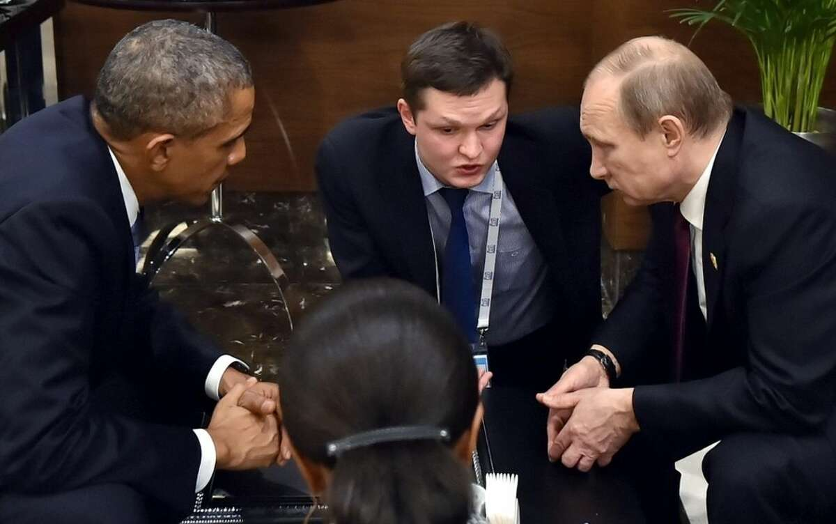 FILE - In this Sunday, Nov. 15, 2015, file photo, U.S. President Barack Obama, left, speaks with Russian President Vladimir Putin, right prior to the opening session of the G-20 summit in Antalya, Turkey. For President Vladimir Putin, the terror attacks in Paris marked a watershed moment in relations with the West. This week's summit in Turkey made it clear that the U.S. and its allies have warmed to the idea of closer ties with Russia, whose help they need to confront the challenge of the Islamic State group. (SPUTNIK, Kremlin Pool Photo via AP, file)