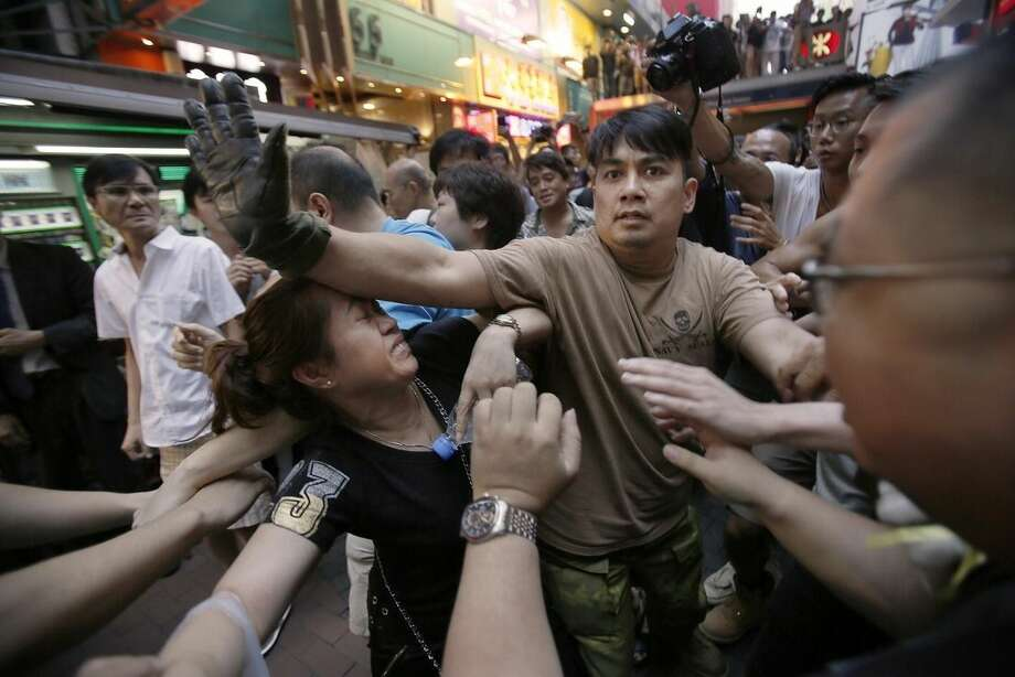 A woman is protected from the crowd by pro-democracy student protesters after a scuffle with local residents in Mong Kok, Hong Kong, Saturday, Oct. 4, 2014. Friction between pro-democracy protesters and opponents of their weeklong occupation of major Hong Kong streets persisted Saturday as police denied they had any connection to criminal gangs suspected of inciting attacks on largely peaceful demonstrators. (AP Photo/Wally Santana)