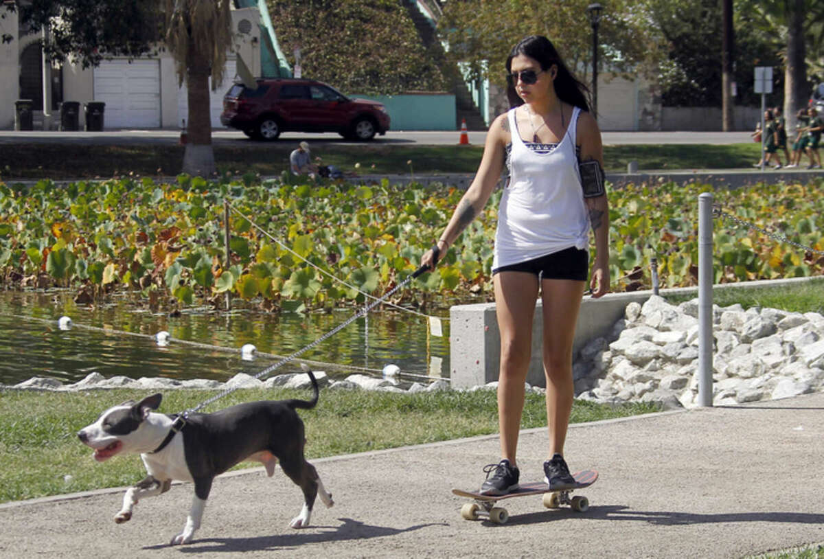 A resident and her dog enjoy the hot weather at Echo Park in Los Angeles, Friday, Oct 3, 2014. As high temperatures were ranging from the low 100s in Southern California to the 90s in the normally more temperate San Francisco Bay Area on Friday, National Weather Service forecasters warned it was just a warm-up for what lies ahead this weekend. (AP Photo/Nick Ut)