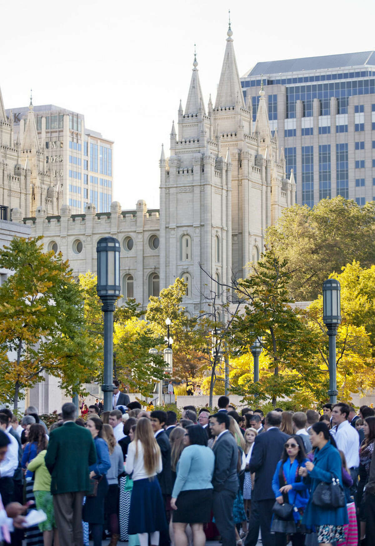 People wait in line outside of the The Church of Jesus Christ of Latter-day Saints' Conference Center with the Salt Lake Temple in the background to before the opening session of the two-day Mormon church conference Saturday, Oct. 4, 2014, in Salt Lake City. Chi Hong Wong, a Mormon leader from Hong Kong delivered a speech in Mandarin on Saturday in what marked the first time in the history of the faith's signature conference that an address was delivered in a language other than English. (AP Photo/Kim Raff)