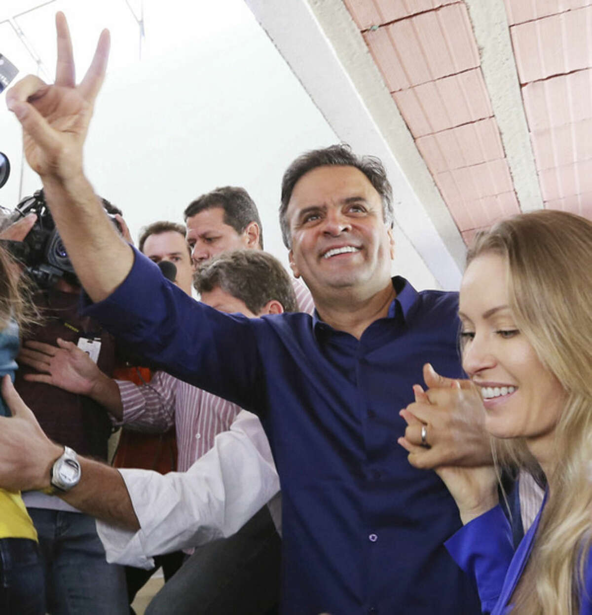 In this photo released by Coligacao Muda Brasil, Aecio Neves, presidential candidate of the Brazilian Social Democracy Party, PSDB, right, and his wife Leticia Weber flash a victory sign during general elections in Belo Horizonte, Brazil, Sunday, Oct. 5, 2014. An exit poll showed Sunday that President Dilma Rousseff will face challenger Aecio Neves in a second-round vote in Brazil's most unpredictable presidential election since the nation's return to democracy nearly three decades ago. (AP Photo/Marcos Fernandes-Coligacao Muda Brasil)