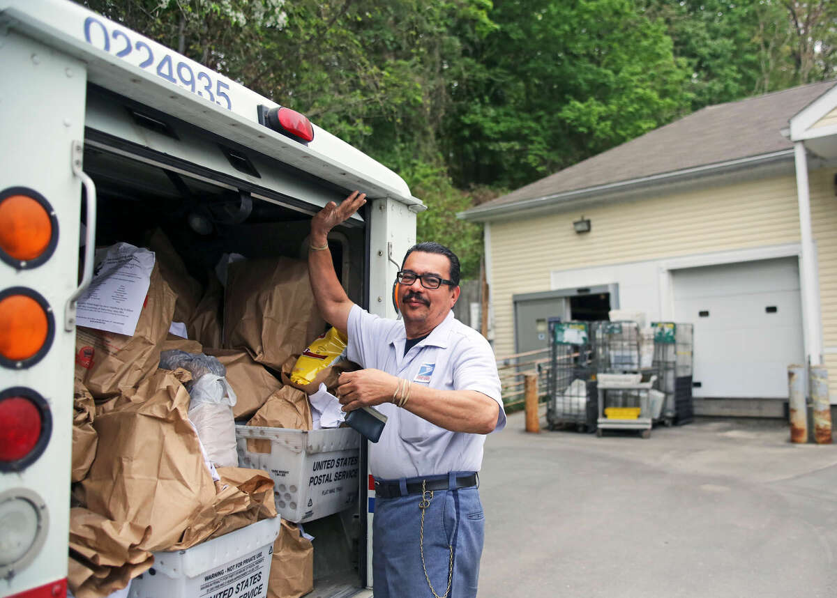 Rafael Colon prepares to unload his mail truck at the Wilton Post Office for the National Association of Letter Carriers Food Drive Saturday afternoon. Hour Photo / Danielle Calloway