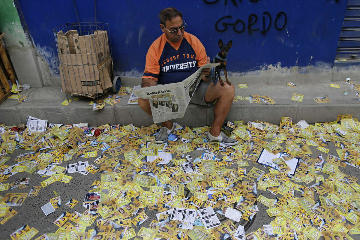 A man with his dog on his knee reads a newspaper on a sidewalk littered with campaign propaganda during general elections in the Complexo do Alemao slum of Rio de Janeiro, Brazil, Sunday, Oct. 5, 2014. Brazilians are casting ballots in a presidential election expected to force a runoff campaign between incumbent Dilma Rousseff and one of her two top challengers. Brazilians are also deciding congressional races and electing governors. (AP Photo/Leo Correa)